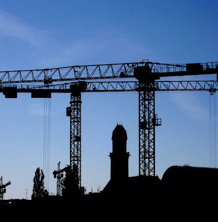Silhouette of some construction cranes against a background of a darkening blue sky. Stock Photo