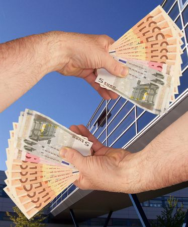 An image of hands holding out a wads of cash in front of a corperate office building facility Stock Photo - 1092040