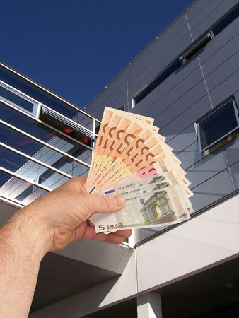 An image of a hand holding out a wad of cash in front of a corperate office building facility Stock Photo - 1092041