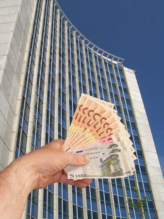 Una imagen de una mano la celebración de un taco de dinero en efectivo frente a un edificio de oficinas corperate instalación  Foto de archivo - 1092043