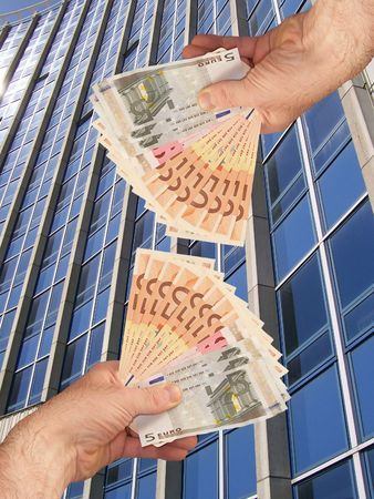 An image of hands holding out a wads of cash in front of a corperate office building facility Stock Photo - 1092044