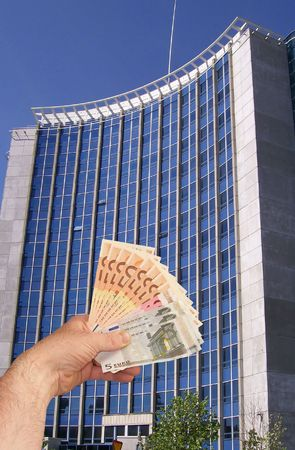 An image of a hand holding out a wad of cash in front of a corperate office building facility Stock Photo - 1092045