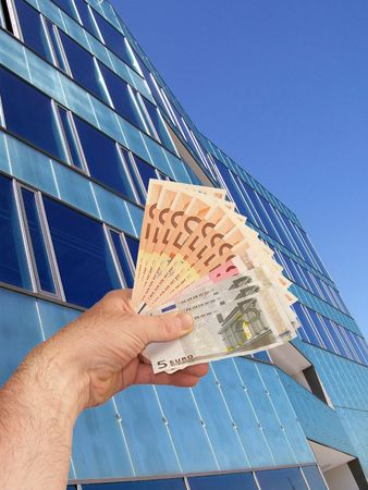 An image of a hand holding out a wad of cash in front of a corperate office building facility Stock Photo - 1092048