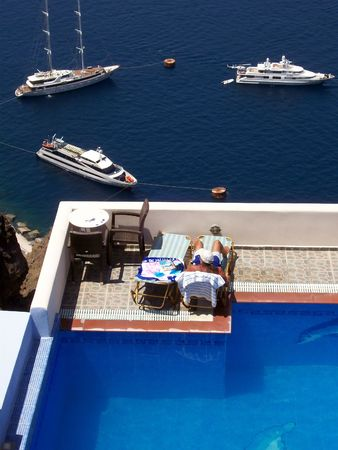 beautiful swimming pool with sunbather in the village of fira overlooking the caldera of santorini Stock Photo - 1105503