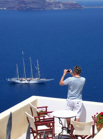 tourist taking a holiday snap of a boat in santorini