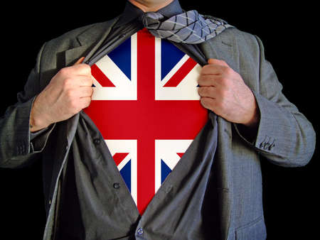 A business man isolated against a black background tearing open his shirt to reveal a  british flag on a t shirt Stock Photo