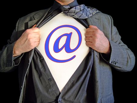 open shirt: A business man isolated against a black background tearing open his shirt to reveal a  email sign on a t shirt Stock Photo