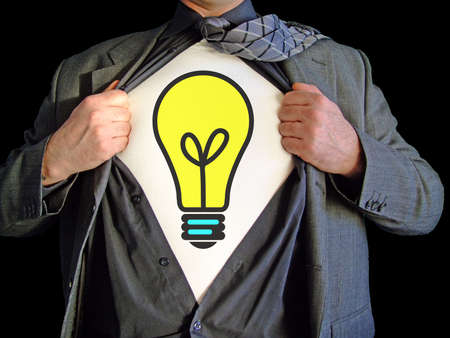 t bulb: A business man isolated against a black background tearing open his shirt to reveal a light bulb on a t shirt Stock Photo