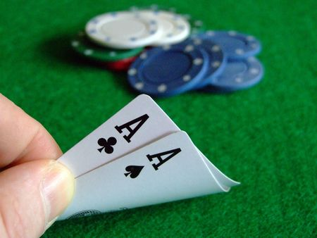 jack of clubs: players hand having a peek at a lucky deal on a poker table