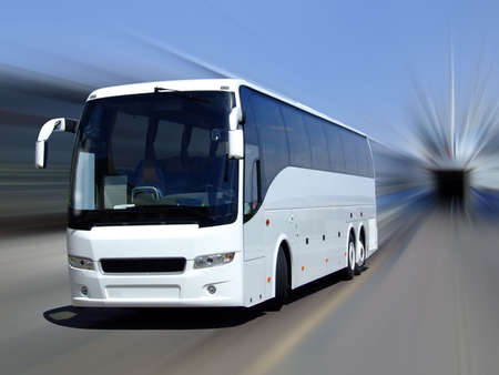 A white tour bus set against a motion blurred background photo