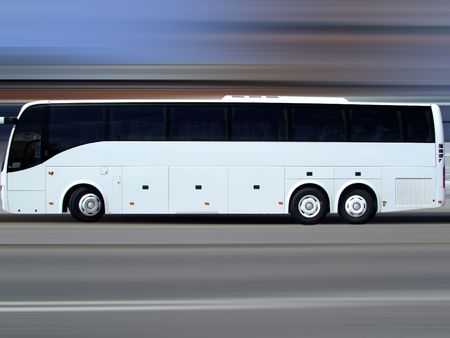 A white tour bus set against a motion blurred background Stock Photo