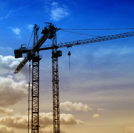 a couple of cranes on a construction site with a blue evening sky backdrop Stock Photo