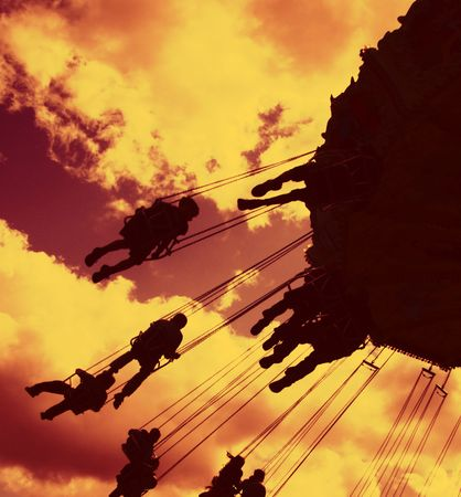 fairground: fairground rides silhouetted against a filtered evening sky