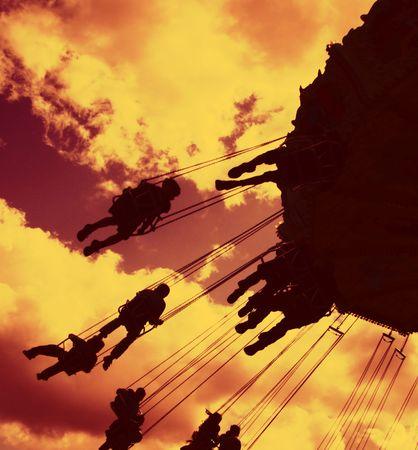 filtered: silhouetted atracciones de feria en contra de un filtrado noche cielo  Foto de archivo