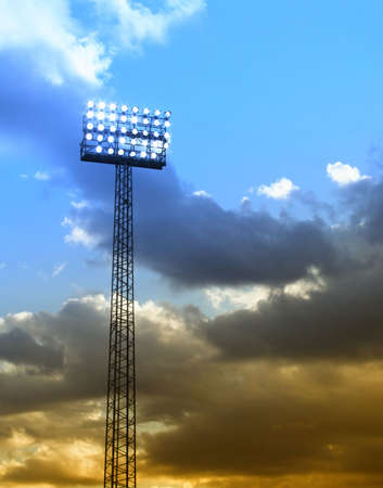 baseball stadium: a football stadium floodlights set against a summer sunset sky