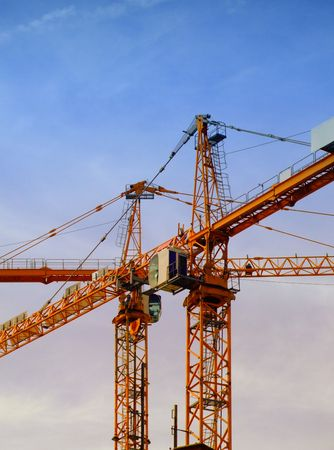 poleas: un par de grúas de construcción en un sitio con un cielo azul telón de fondo  Foto de archivo