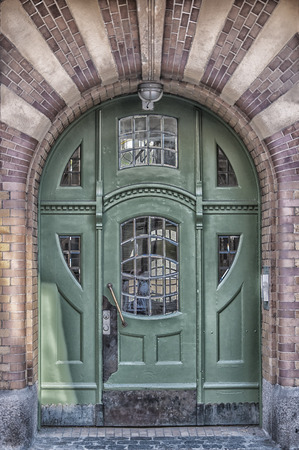 An art deco style entrance painted green situated in the Swedish town of Ystad. photo