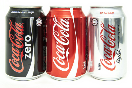 HELSINGBORG, SWEDEN - January 21, 2014: 0,33l Assorted Coca-Cola cans Isolated On White Background. Coca-Cola is a carbonated soft drink sold in shops, restaurants, and vending machines around the globe.