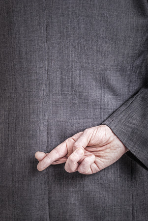 A conceptial image of a business man with his fingers crossed behind his back. photo