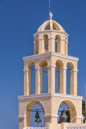 A peach and white colored bell tower from Oia on the greek isle of Santorini. photo