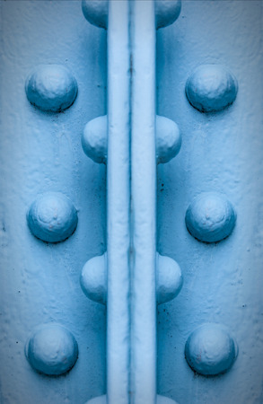 girders: A textured grungy background image of blue painted metal girders and rivets.