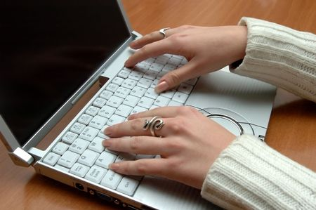 small laptop & lady hands on the wood desktop Stock Photo