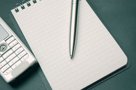 clean sheet of notebook, pen and phones on dark-gray background. close-up photos photo