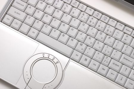Keyboard of silvery hi-end modern laptop with round touchpad photo