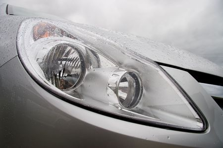 sullenly: Hood of modern car after rain with drops on a headlight and body. Cloudy wheather.