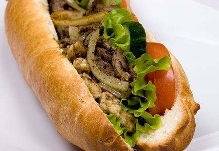A french sub sandwich with the fried meat, lettuce, bow and tomatoes. Close-up photo Stock Photo