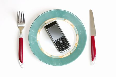 Modern cellular phone (smartphone) on a dish, in surroundings a knife and fork Stock Photo - 1963572