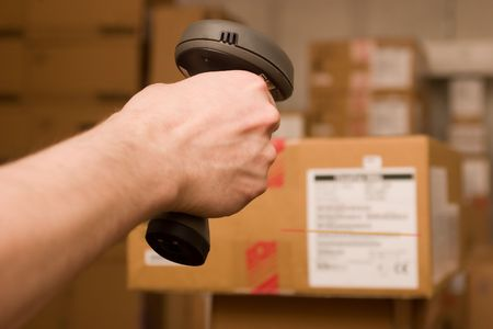 A man gets on the hip scaner in operations directed on printed barcode. Warehouse scene. Stock Photo