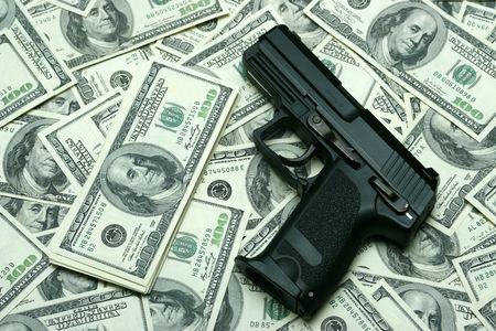 gun shot: Black gun on 100-bucks background. Clos-Up studio shot. Stock Photo