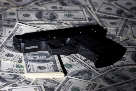 hardly: Black gun on 100-bucks background. Hardly directed ighted. Clos-Up studio shot. Stock Photo
