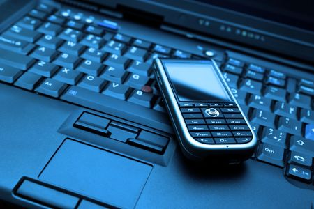 Blue-toned keyboard of high-end laptop and modern smartphone on it. RAW and Tiff also available on demand. photo