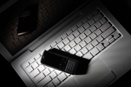 Modern elegance laptop and cellular phone on it. In the beam of light. photo