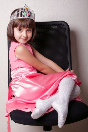 Cherfull girl of 8 years old with corona on a black chair. There are pink clothes on a girl.