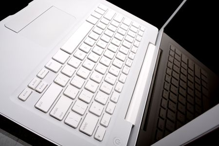 White laptop with keyboard reflection on display.