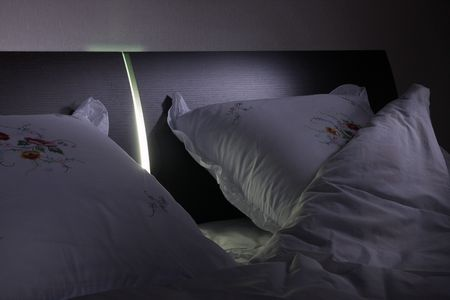 bed frame: Empty night double bed in lamp light Stock Photo