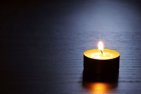 Single candle on a dark wooden table in back lit.