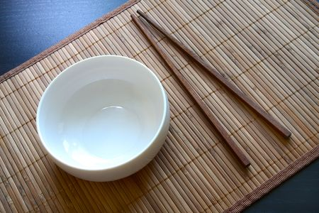 Oriental serving. White empty dish and chopsticks on bamboo matt. Above view. photo