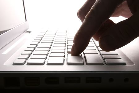 Man pressed key on white laptop in backlit. Close-up scene. photo