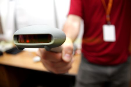 Man with bar code reader in action. Selective focus (shallow DOF). Stock Photo