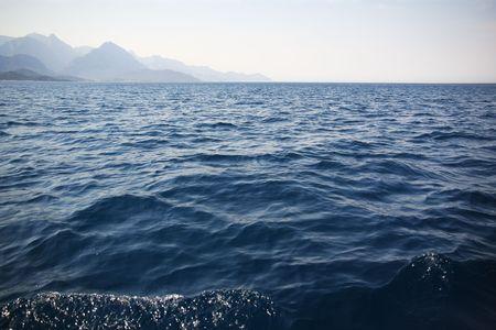 Seascape. Blue waves and mountains on horizon. Mediterranean. Stock Photo - 4989311