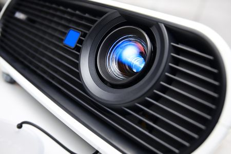 tilt: Face of white multimedia projector. Close-up lens. Nobody. Tilt view with shallow DOF. Stock Photo