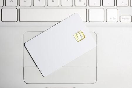 smart card: Modern security. White empty smart card close-up on laptop. Stock Photo