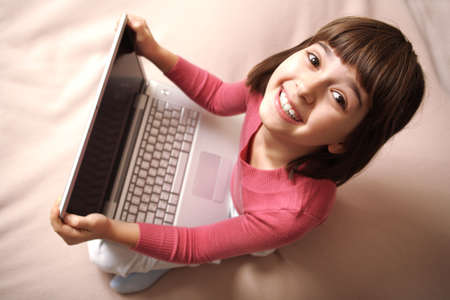 A caucasian girl holds laptop and laughs. Top view.