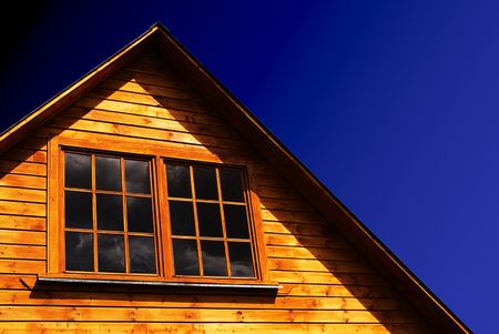 The roof of a rural wooden house on a blue sky background.
