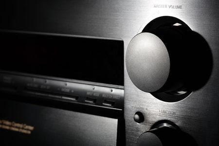 Black home theater amplifier volume knob. Close-up shot in floodlit. Shallow DOF.