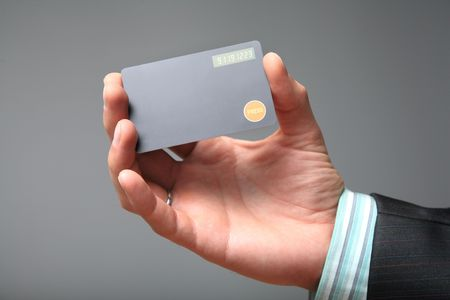 authenticate: Displaycard Token with the button and one-time password on screen in the hands of a businessman. Grey background.